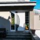 Eingang eines grauen Einfamilienhauses mit moderner weißer Coplaning Haustür.
