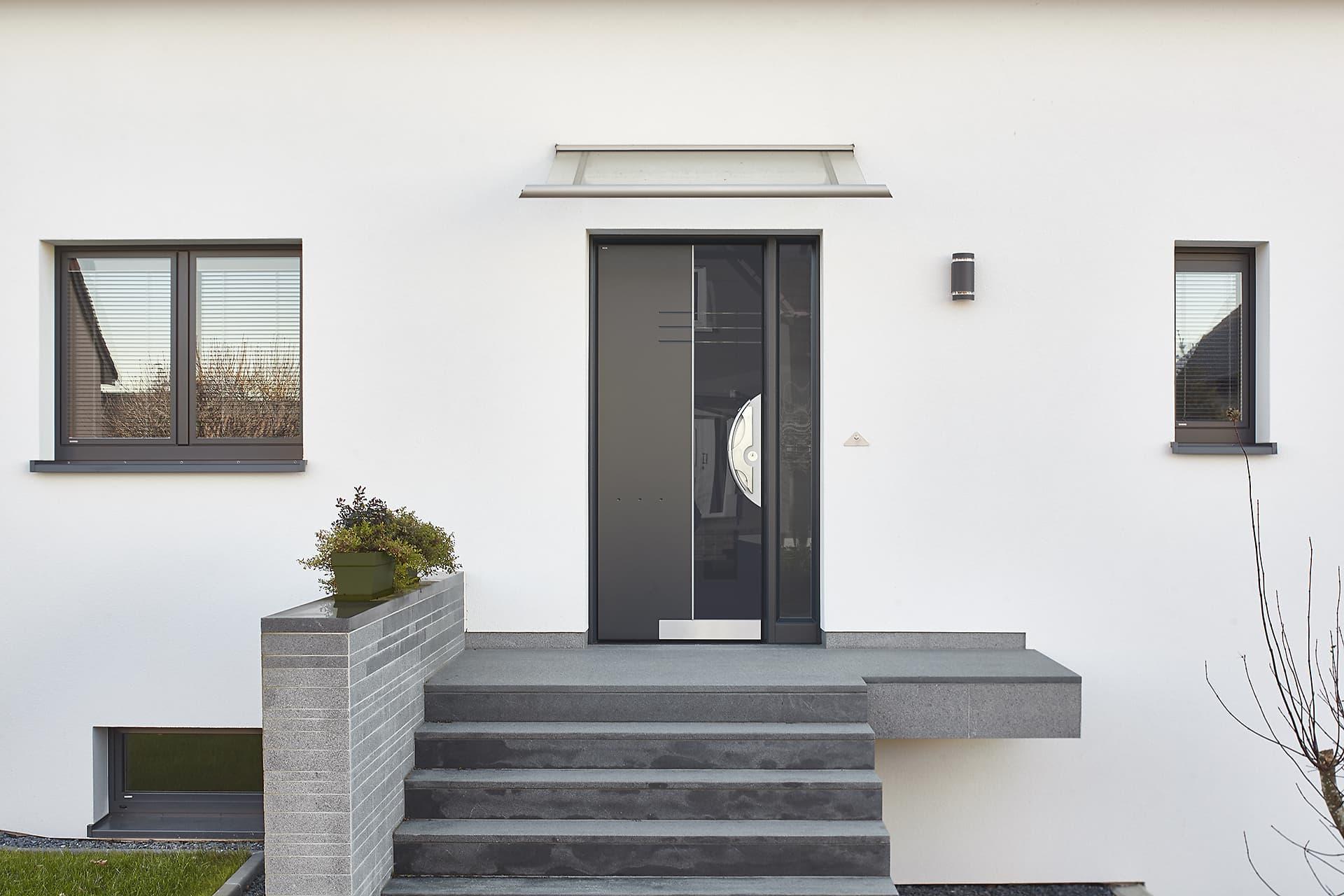 Nahaufnahme des Eingangsbereichs eines weißen Einfamilienhauses mit Blick auf die graue Coplaning Haustür mit rechts und links grauen Coplaning Alu Fenster.
