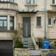 Einfamilienhaus mit Steinfassade mit einer grauen Coplaning Aluminium Haustür und grauen Coplaning Jalousienfenster mit deckensektionaltor.