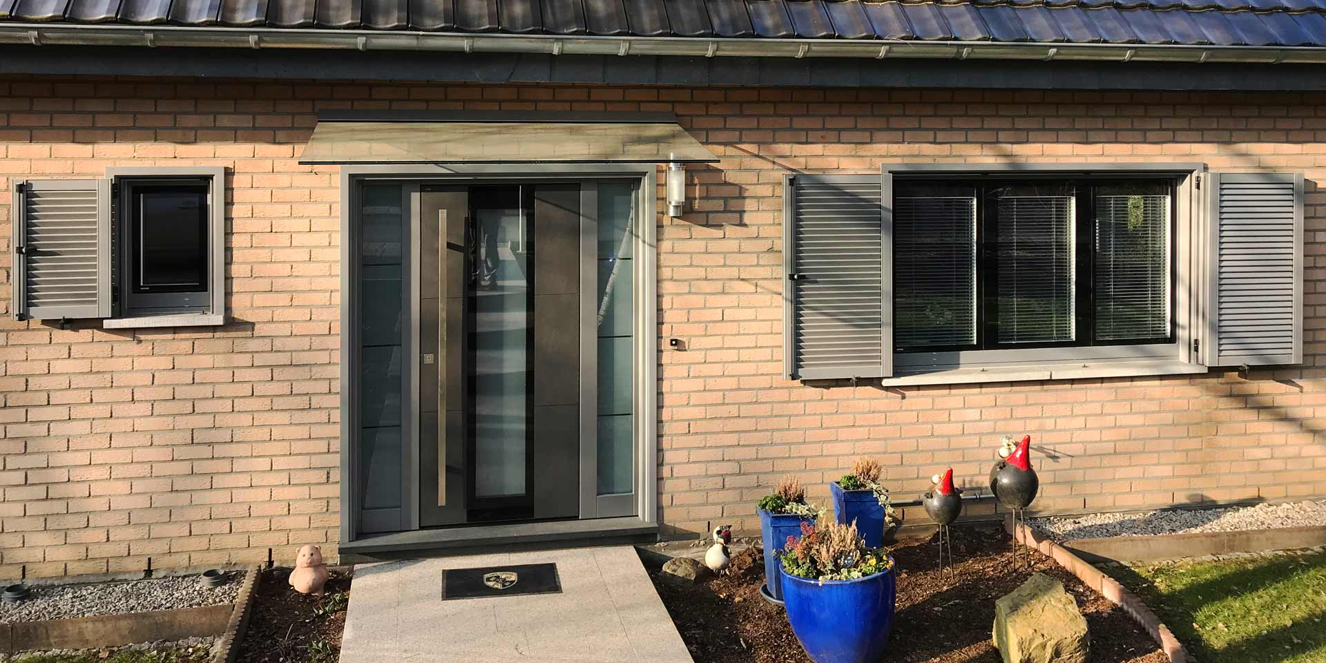 Nahaufnahme des Eingangsbereichs eines Einfamilienhauses mit Steinfassade mit Blick auf eine graue Coplaning Keramik Haustür und jeweils links und rechts davon ein graues Coplaning Holzfenster mit passenden Klappläden.