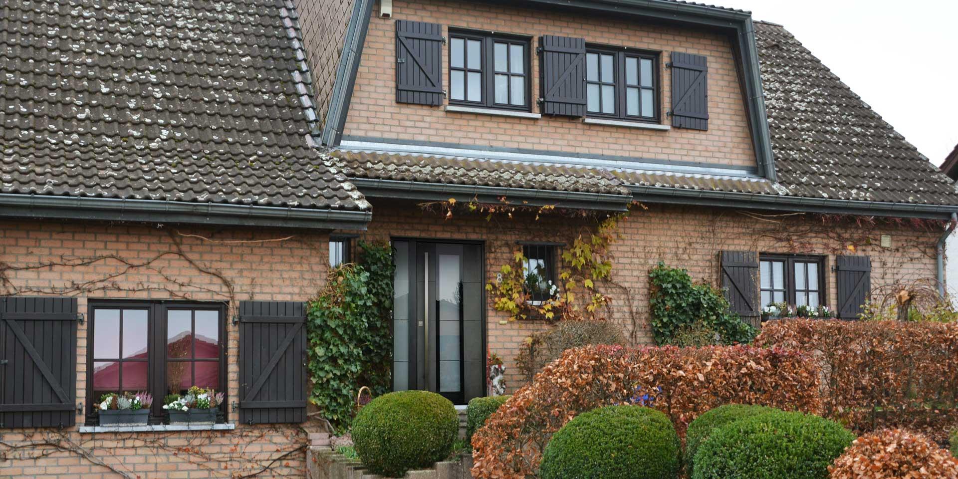 Einfamilienhaus mit Steinfassade mit einer grauen Coplaning Keramik Haustür.