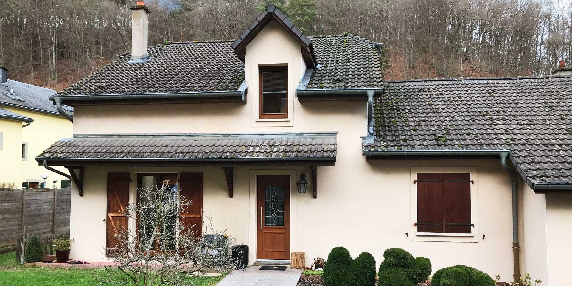 Beiges Einfamilienhaus mit brauner Coplaning Haustür und links, rechts und darüber, passende braune Coplaning Alu Fenster