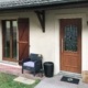 Nahaufnahme vom Eingangsbereich des beigen Einfamilienhauses. Man sieht die Coplaning Haustür aus Holz und links davon passende braune Coplaning Alu Fenster.