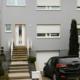 Graues Einfamilienhaus mit neuer moderner weißer Coplaning Haustür.