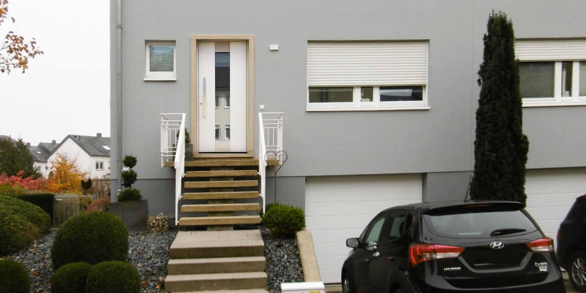 Nahaufnahme des Eingangsbereichs eines grauen Einfamilienhauses mit neuer moderner weißer Coplaning Haustür.