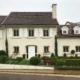 Gelbliches Einfamilienhaus mit moderner weißer Coplaning Haustür und weiße Coplaning Holzfenster mit weißen Klappläden.