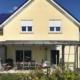 Gelbes Einfamilienhaus mit einer Coplaning Terassenüberdachung mit Glasdach und grauen Alu Senkrechtmarkise.